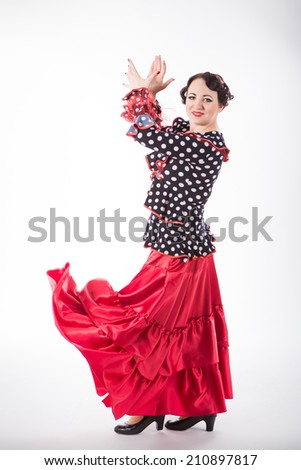 young beautiful brunette female spanish flamenco dancer in black shirt and red flamenco skirt dancing with her arms and flying red skirt in studio on gray background - stock photo