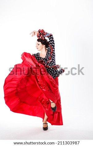 young beautiful brunette female spanish flamenco dancer in black shirt and red flamenco skirt dancing with fan red in her arms in studio on gray background - stock photo