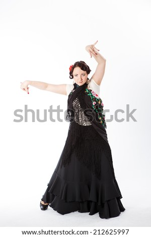 young beautiful brunette female spanish flamenco dancer in white blouse and black flamenco skirt dancing with black flower shawl in her arms in studio on gray background - stock photo