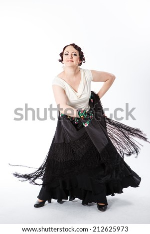 young beautiful brunette female spanish flamenco dancer in white shirt and black flamenco skirt dancing with black flower shawl in her arms in studio on gray background - stock photo