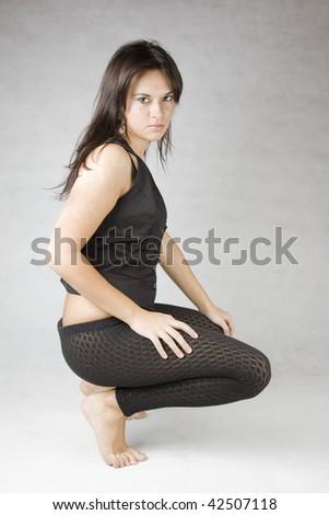 young beautiful brunette girl crouching on the floor - stock photo