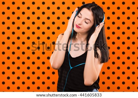 Young beautiful brunette girl, in black blouse, listening to music with big blue headphones on orange background with black dots - stock photo