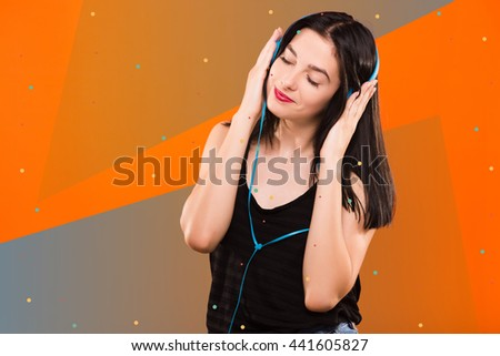 Young beautiful brunette girl, in black blouse, listening to music with big headphones on geometric orange and gray background with blue and white dots - stock photo