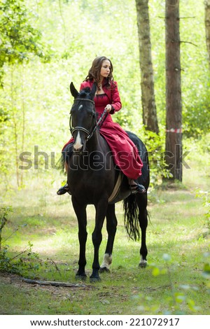 young beautiful brunette girl in red dress ride on the black horse in green forest - stock photo