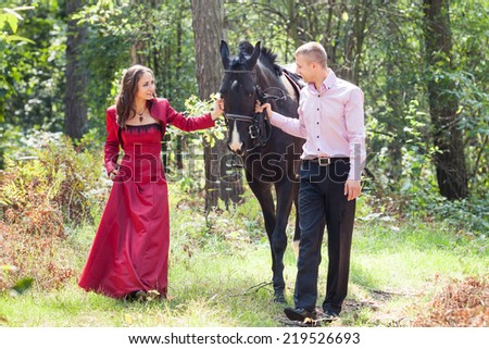 young beautiful brunette girl  in red dress walk with handsome man in pink shirt hold black horse in green forest - stock photo