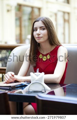 Young beautiful brunette girl sitting in a coffee shop - stock photo