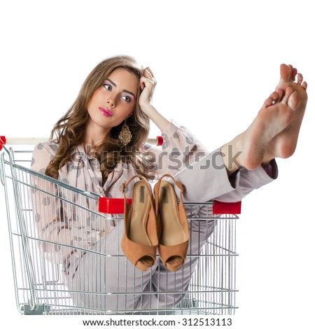 Young beautiful brunette girl sitting in an empty shopping trolley, isolated on white background - stock photo