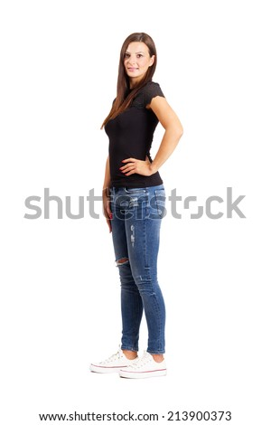 Young beautiful brunette posing with arms on her hips.  Full body length isolated over white. - stock photo