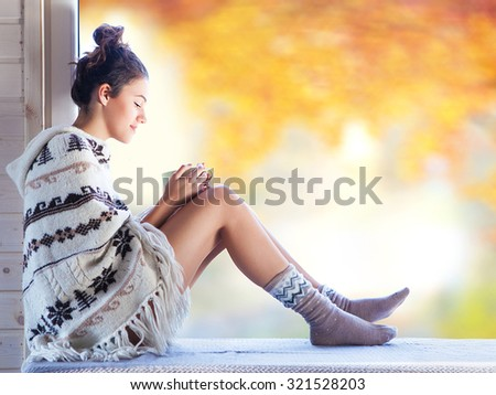 Young beautiful brunette smiling woman with cup of coffee wearing knitted nordic print poncho sitting home by the window. Blurred garden fall background. - stock photo