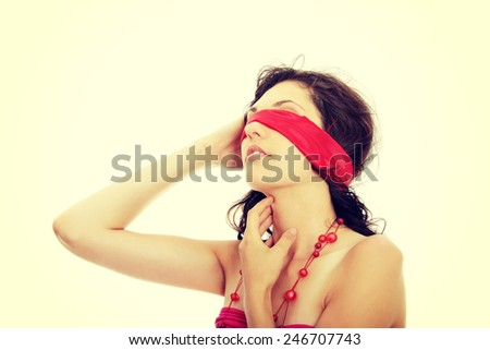 Young beautiful brunette with red eyeband and necklace.  - stock photo