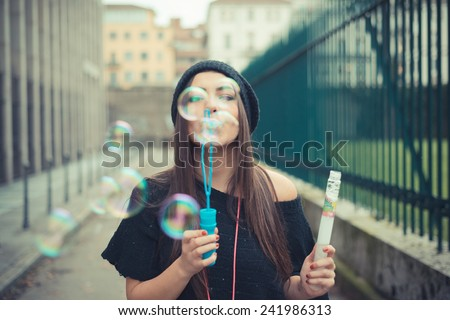 young beautiful brunette woman girl blowing bubbles soup outdoor - stock photo