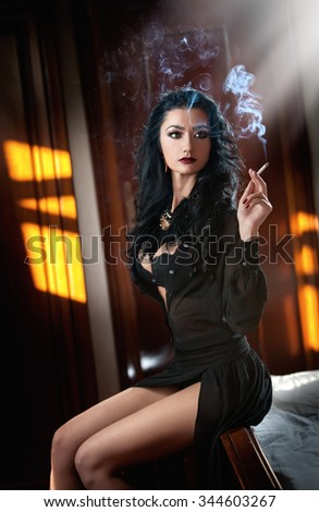 Young beautiful brunette woman in black dress relaxing on the in vintage scenery. Romantic mysterious young lady holding sensually a cigarette, boudoir shot. Dark hair female smoking in bedroom - stock photo