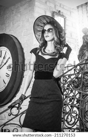 Young beautiful brunette woman in black standing on stairs near an over sized wall clock. Elegant romantic mysterious lady with movie star look in luxurious vintage interior, black and white photo. - stock photo