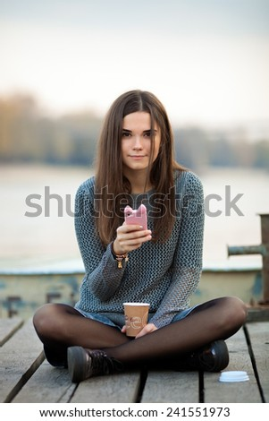 Young beautiful brunette woman in blouse and denim skirt sitting on the river pier with coffee and using her smartphone - stock photo