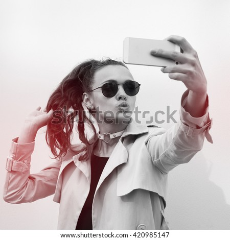 Young beautiful brunette woman in casual style clothes talking on her phone and making selfie with her mobile camera. Portrait of attractive fashion looking girl model. Hipster. - stock photo