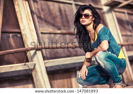 Young beautiful brunette woman in sunglasses sitting behind texture wall. - stock photo