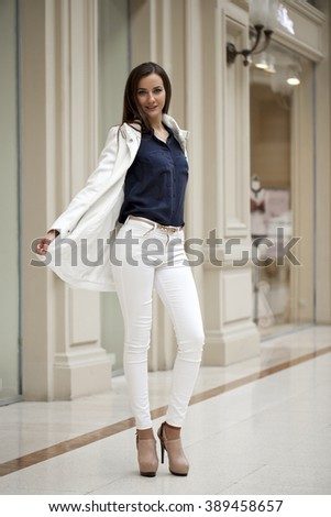 Young beautiful brunette woman in white pants and jacket and walk the mall - stock photo