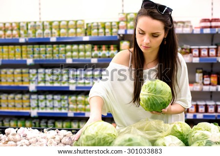 Young beautiful brunette woman is choosing a white cabbage in the store, on the shelves with products background - stock photo
