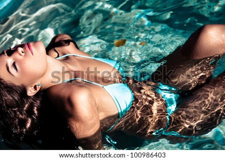 young beautiful brunette woman resting in the swimming pool on the sunny day - stock photo