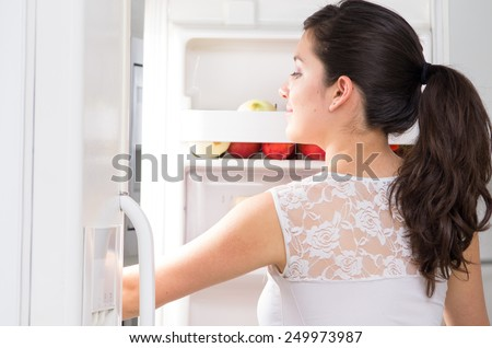 young beautiful brunette woman searching for food in the fridge - stock photo