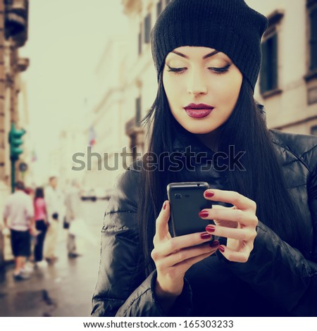 Young beautiful brunette woman touching and browsing her smart phone over city background, toned - stock photo