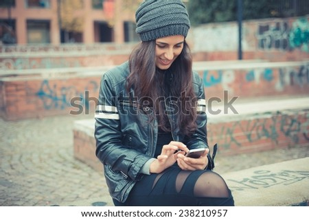 young beautiful brunette woman using smartphone in the city - stock photo