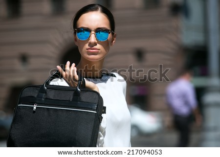 Young beautiful brunette woman with a bag in his hand - stock photo