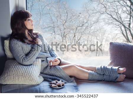 Young beautiful brunette woman with cup of coffee and gingerbread wearing knitted cardigan sitting home relaxing by the window. Home chill out concept. - stock photo
