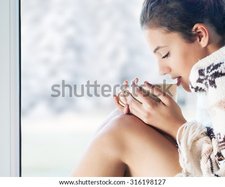 Young beautiful  brunette woman with cup of coffee wearing knitted nordic print poncho sitting home by the window. Blurred  winter snow tree background.  - stock photo