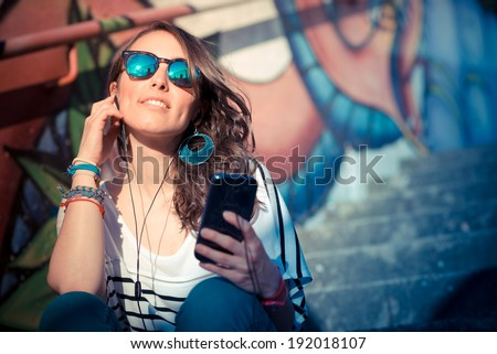 young beautiful brunette woman with smart phone listening music in the city - stock photo