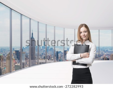 Young beautiful business lady is holding a black document case. New York panoramic office. A concept of legal services. - stock photo