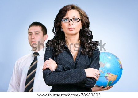 Young beautiful business woman agains the man with globe - stock photo