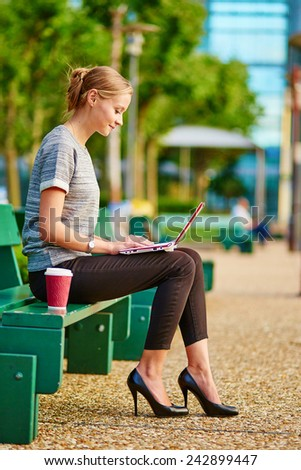 Young beautiful business woman drinking coffee and working on her laptop outdoors  - stock photo