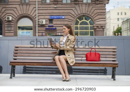 Young beautiful business woman sitting on a bench in the summer city - stock photo