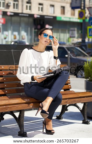 Young beautiful business woman sitting on a bench in the sunny city - stock photo
