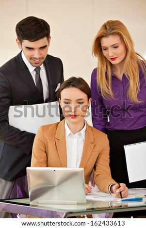 Young beautiful business woman smiling, looking at laptop and two colleagues business people in the back - stock photo