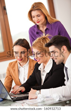 Young beautiful business woman smiling with a laptop in front of her and three colleagues business people around her - stock photo