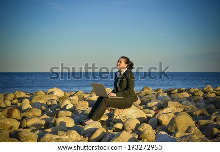 young beautiful business woman wearing suit in front of the sea working on computer sitting on the rocks at the beach under a blue sky - stock photo