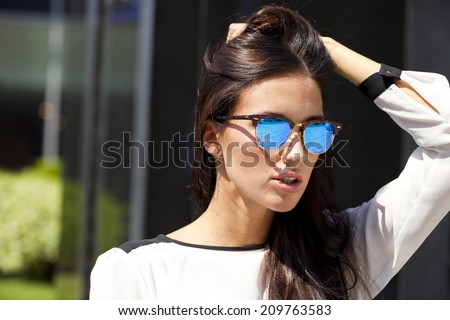Young beautiful business woman with blue mirrored sunglasses - stock photo