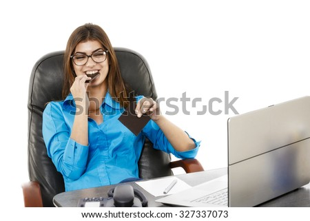 Young beautiful businesswoman eating chocolate at her workplace in office - stock photo