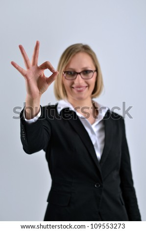 Young beautiful businesswoman hand gesturing okay sign - stock photo