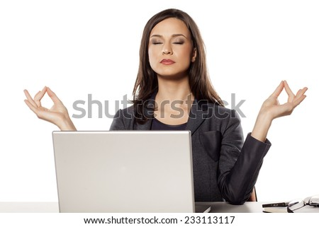 young beautiful businesswoman meditates on her workplace - stock photo