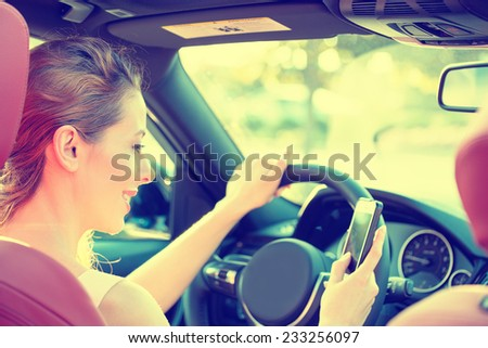 Young beautiful businesswoman sending a text message using mobile phone while driving car to work. Risky, reckless driver bad habits. Traffic safety rule violation lack of attention concept  - stock photo