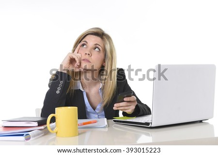 young beautiful businesswoman suffering stress working at office computer desk feeling tired and bored  looking overworked using mobile phone in business mess - stock photo