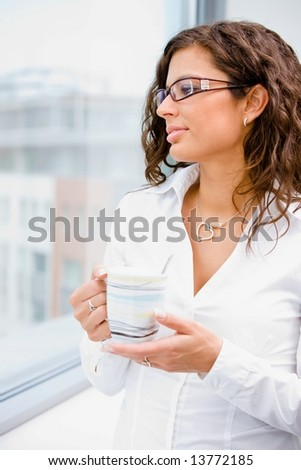 Young beautiful businesswoman taking break, standing in front of office window, holding coffee cup, looking away, smiling. - stock photo