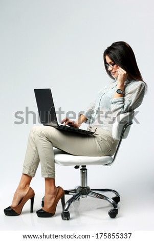 Young beautiful businesswoman using laptop and talking on the phone on gray background - stock photo