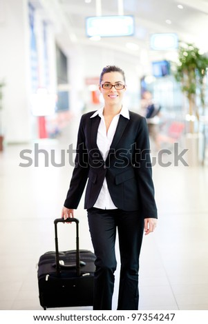 young beautiful businesswoman walking in airport with luggage - stock photo