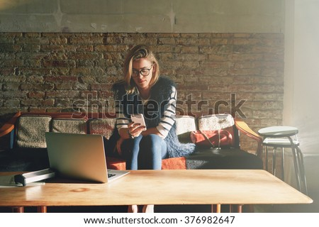 young beautiful businesswoman writes a message on her smart-phone during the lunch break. Attractive female student doing homework in a coffee-shop - stock photo