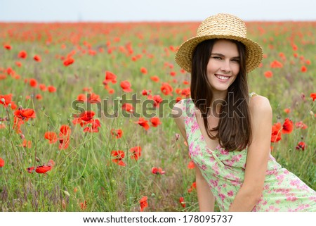 Young beautiful calm girl in straw hat dreaming on a poppy field, summer outdoor. - stock photo