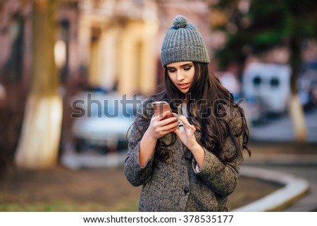 Young beautiful casual girl calling on her cell phone  in jacket and hat, smile on  spring city street  lifestyle on background .  Spring street look. - stock photo